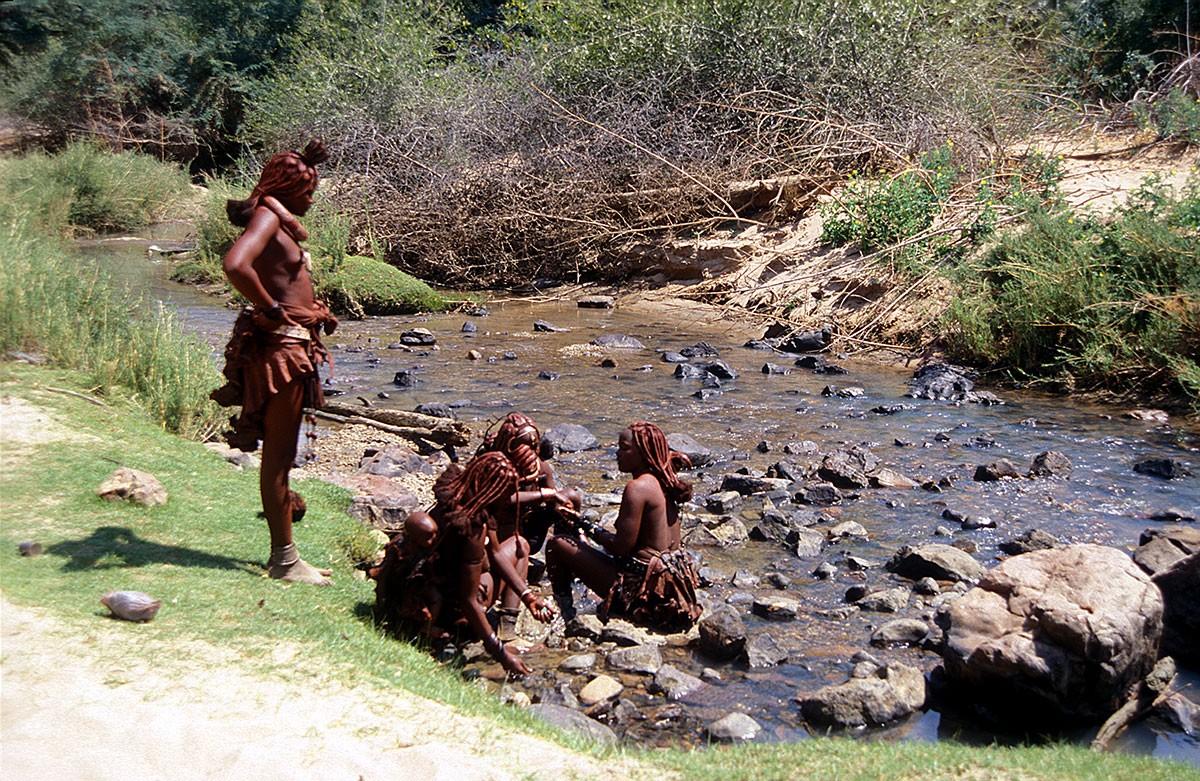 Namibia mujeres himba acicalandose a la orilla del rio