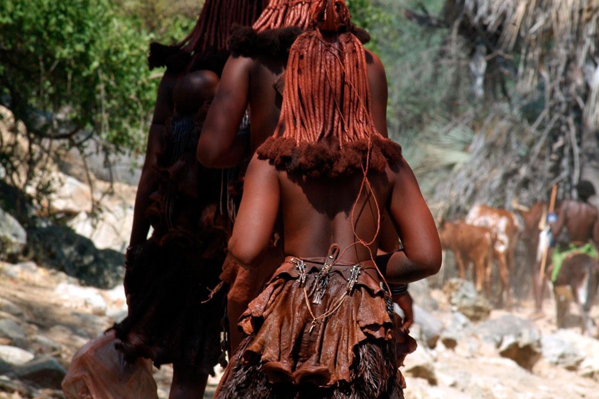 Namibia mujeres caminando hacia nuevo asentamiento al fondo los hombres y el ganado.